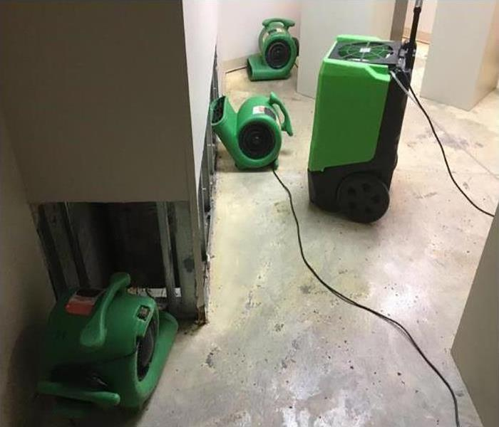 Two dehumidifiers and two air movers drying up water damage in a hallway