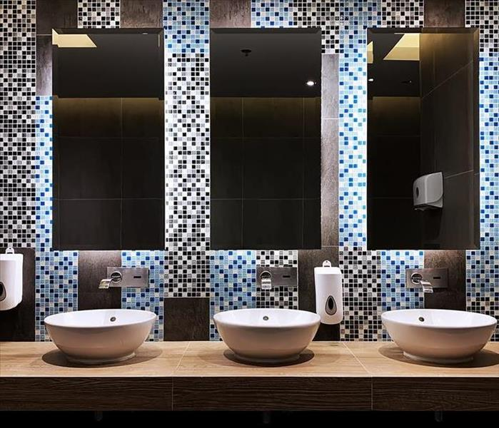 A commercial bathroom with three sinks and three mirrors.